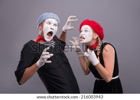 Waist-up horizontal portrait of couple of two mimes standing face to face and screaming on each other and showing horror with their hands isolated on grey background with copy place - stock photo