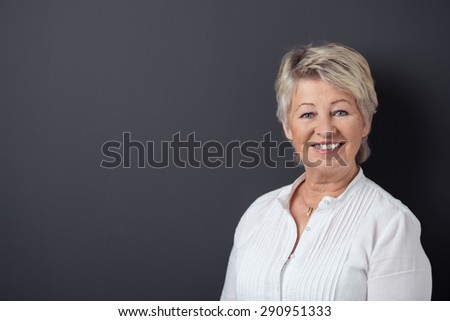 Waist up of attractive smiling senior blonde woman wearing white shirt, looking at camera on black background - stock photo
