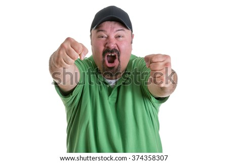Waist Up of Excited Man Wearing Green Shirt and Baseball Cap Pumping Fists Toward Camera While Celebrating Team Win in Studio with White Background - stock photo