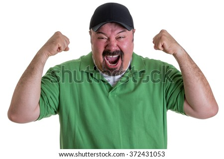 Waist Up of Excited Man with Goatee Wearing Green Shirt and Baseball Cap Holding Fists in Air and Celebrating Team Win in Studio with White Background - stock photo