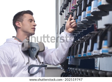 waist up of man selecting car paint. closeup of man wearing overall and working in shop - stock photo