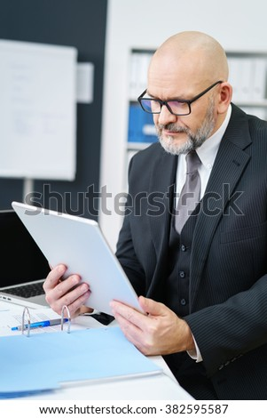 Waist Up of Mature Professional Businessman Wearing Suit and Eyeglasses Looking Down with Serious Expression at Tablet Computer While Sitting at Desk in Modern Office Workplace - stock photo