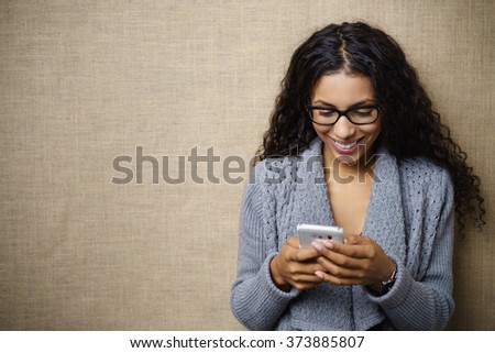 Waist Up of Professional Smiling Young Woman Wearing Cozy Gray Sweater Cardigan and Looking Down at Cell Phone in Studio with Textured Beige Background and Copy Space - stock photo