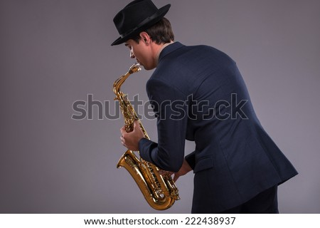Waist-up portrait of a young handsome Caucasian jazz man in a suit with a black hat looking at the camera with astonishment holding a trumpet in his hand isolated on grey background with copy place - stock photo