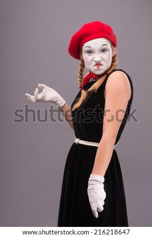 Waist-up portrait of angry female mime in red head and with white face showing with her hands horror isolated on grey background with copy place - stock photo
