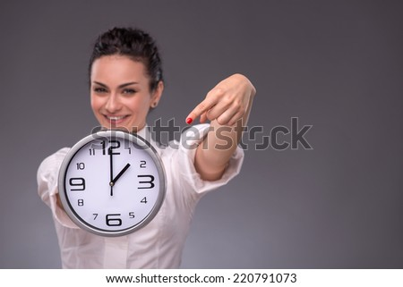 Waist-up portrait of beautiful smiling girl holding a big clock in her hands and looking at the camera, with selective focus on a clock isolated on grey background with copy place - stock photo