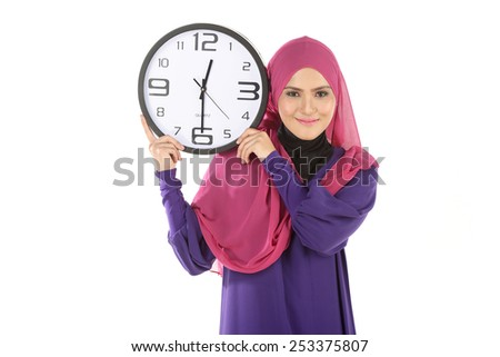 Waist-up portrait of beautiful smiling Muslim girl holding with pleasure a big clock in her hands - stock photo