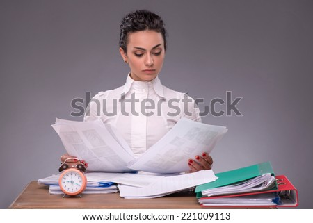 Waist-up portrait of concentrated girl sitting at the table in office with a pile of documents and a clock, isolated on grey background with copy place, concept of time management at work - stock photo