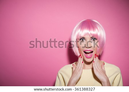 Waist up portrait of crazy girl expressing her surprise. She is standing in pink wig and laughing. The lady is looking at camera with admiration. Isolated and copy space in left side - stock photo