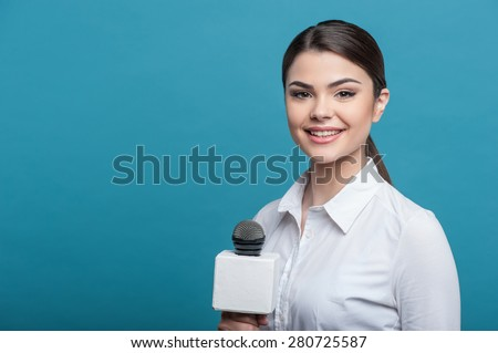Waist up portrait of elegant woman reporter, who interviews and is smiling and looking at the camera holding the microphone. She has long brown hair and a white blouse, isolated on a blue background - stock photo