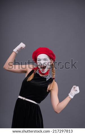 Waist-up portrait of female mime with funny face, red hat and red scarf looking at the camera smiling and showing that she has something done, isolated on grey background with copy place - stock photo