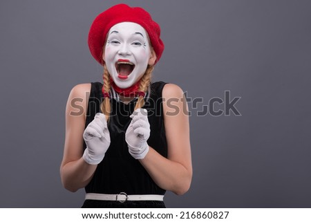 Waist-up portrait of female mime with red hat and white face happy shouting and looking at the camera isolated on grey background with copy place - stock photo