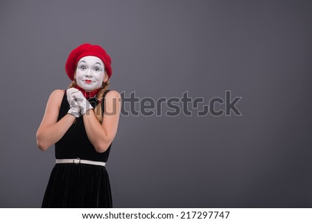 Waist-up portrait of female mime with surprised face, red hat and red scarf looking at the camera and holding her hands on the chest isolated on grey background with copy place - stock photo