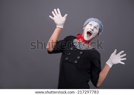 Waist-up portrait of funny male mime with grey hat and white face happy looking up with great surprise and breeding his hands isolated on grey background with copy place - stock photo