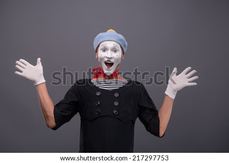 Waist-up portrait of funny male mime with grey hat and white face smiling looking at the camera with great surprise and breeding his hands isolated on grey background with copy place - stock photo