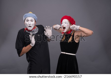 Waist-up portrait of funny mime couple with white faces, female mime closing her ears with her fingers and shouting on male mime carefully waving his hand isolated on grey background - stock photo