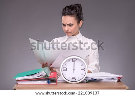 Waist-up portrait of girl sitting at the table in office with a pile of documents and the clock and concentrated reading some papers isolated on grey background with copy place - stock photo