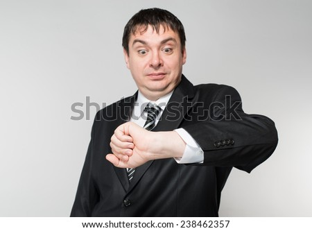 Waist-up portrait of handsome confident businessman standing and touching clock on his hand and looking aside on white background with copy place - stock photo
