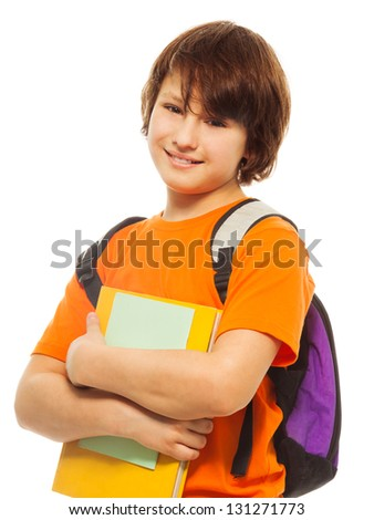 Waist up portrait of happy and smiling teenage boy holding pile of books and wearing backpack on white - stock photo