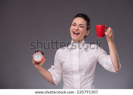Waist- up portrait of happy girl holding an alarm clock and a red cup in her hand looking at the camera with pretty smile isolated on grey background with copy place concept of time management - stock photo