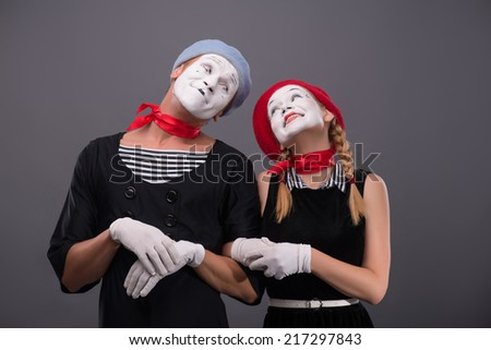Waist-up portrait of mime couple with white faces looking at each other and lovely smiling isolated on grey background with copy place - stock photo
