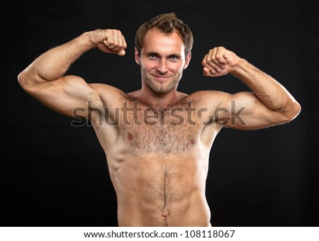 Waist-up portrait of muscular man flexing his biceps against black background - stock photo