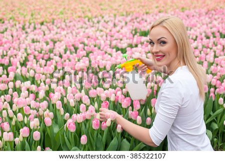 Waist up portrait of pretty young woman pouring water on flowers in plant nursery. She is standing and holding a sprinkler. The florist is looking at camera and smiling - stock photo