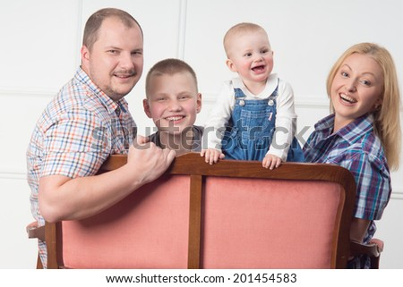 Waist up portrait of smiling parents with two children sitting on sofa and turning to smile at camera, interior background - stock photo