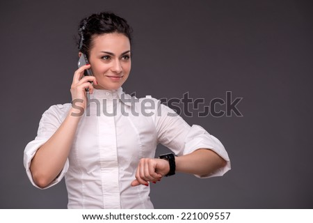 Waist-up portrait of successful businesswoman talking per telephone and looking at the watches and ahead with confidence and smile, isolated on grey background with copy place - stock photo