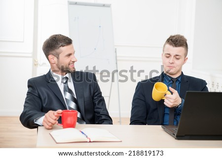 Waist-up portrait of two handsome businessmen in suits having a coffee-break in office sitting at the table and holding cups in their hands, one curiously looking at his cup and another smiling  - stock photo