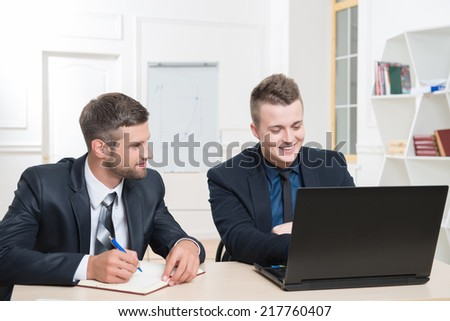 Waist-up portrait of two handsome businessmen in suits sitting at the table and both looking on the screen of laptop in office and smiling, one typing and another writing something at his notebook - stock photo