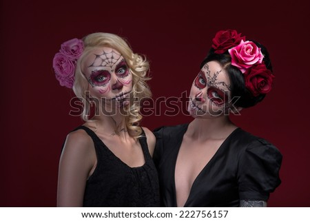 Waist-up portrait of two young girls standing near each other in black dresses with Calaveras makeup and roses in their hair looking at the camera isolated on red background with copy place - stock photo