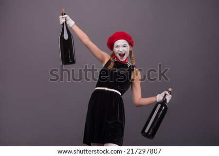 Waist-up Portrait of young drunk mime girl holding big bottles in her hands well smiling and looking at the camera isolated on grey background with copy place - stock photo