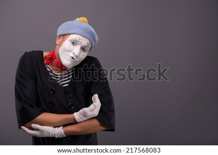 Waist-up Portrait of young mime imagining that he is holding a baby on his hands and lulling it, looking at the camera isolated on grey background with copy place - stock photo