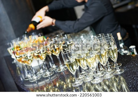Waiter bartender pouring white wine into glasses at party event - stock photo