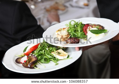 Waiter carrying plates of starters with fresh rocket salad on the way to serve them to guests at a restaurant - stock photo