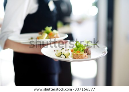 Waiter carrying plates with meat dish on some festive event, party or wedding reception - stock photo