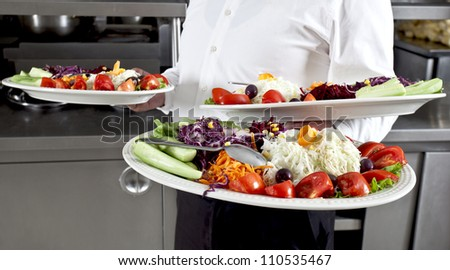 Waiter carrying plates with salad - stock photo