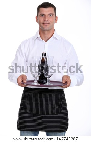 Waiter carrying tray of beer - stock photo