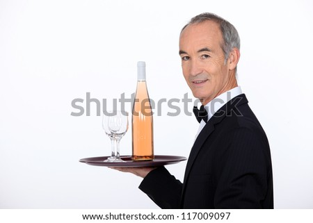 Waiter carrying wine on tray - stock photo