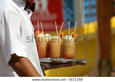 Waiter handling a salver with colorful cocktails. - stock photo
