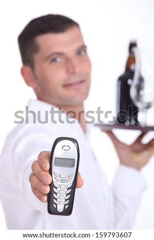 Waiter holding cell phone - stock photo
