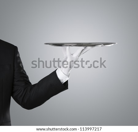 Waiter holding empty silver tray over gray background with copy space - stock photo