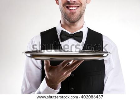 Waiter holding tray. Smiling butler. - stock photo