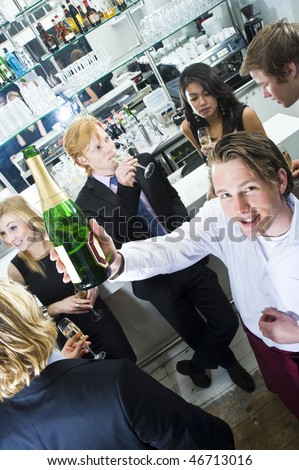 Waiter holding up a bottle of champagne, surrounded by a group of partying people - stock photo