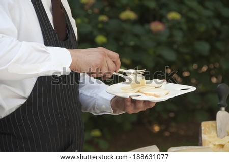 Waiter in uniform serving cheese - stock photo