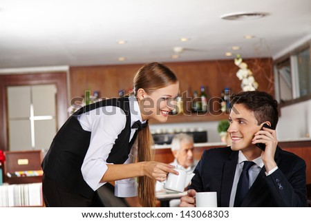 Waiter offering a pot of coffee to business man in hotel caf���© - stock photo
