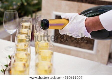 waiter pouring champagne into glasses - stock photo