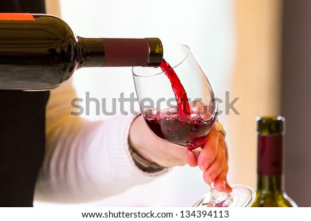 Waiter pouring  red wine - stock photo