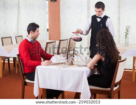 Waiter pouring red wine to couple - stock photo